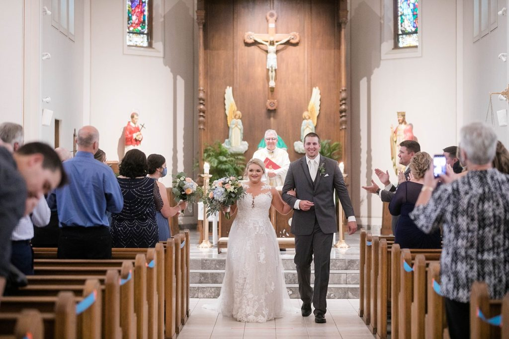 couple smiling during the recessional at St. Charles of Borromeo in Chippewa Falls for their wedding