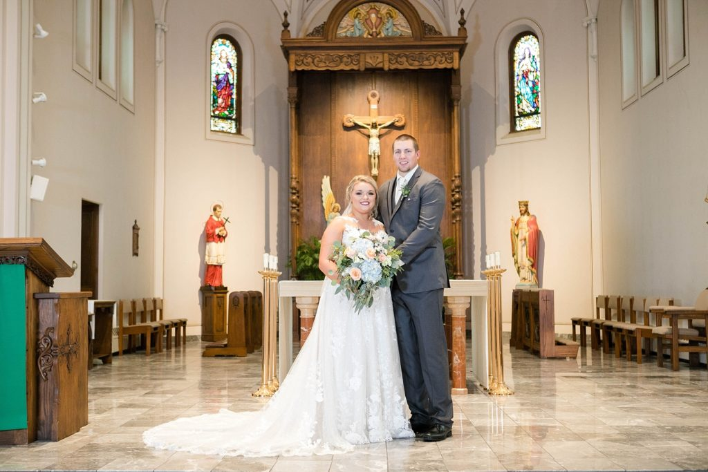 couple smiling in their formal portrait at St. Charles of Borromeo in Chippewa Falls for their wedding
