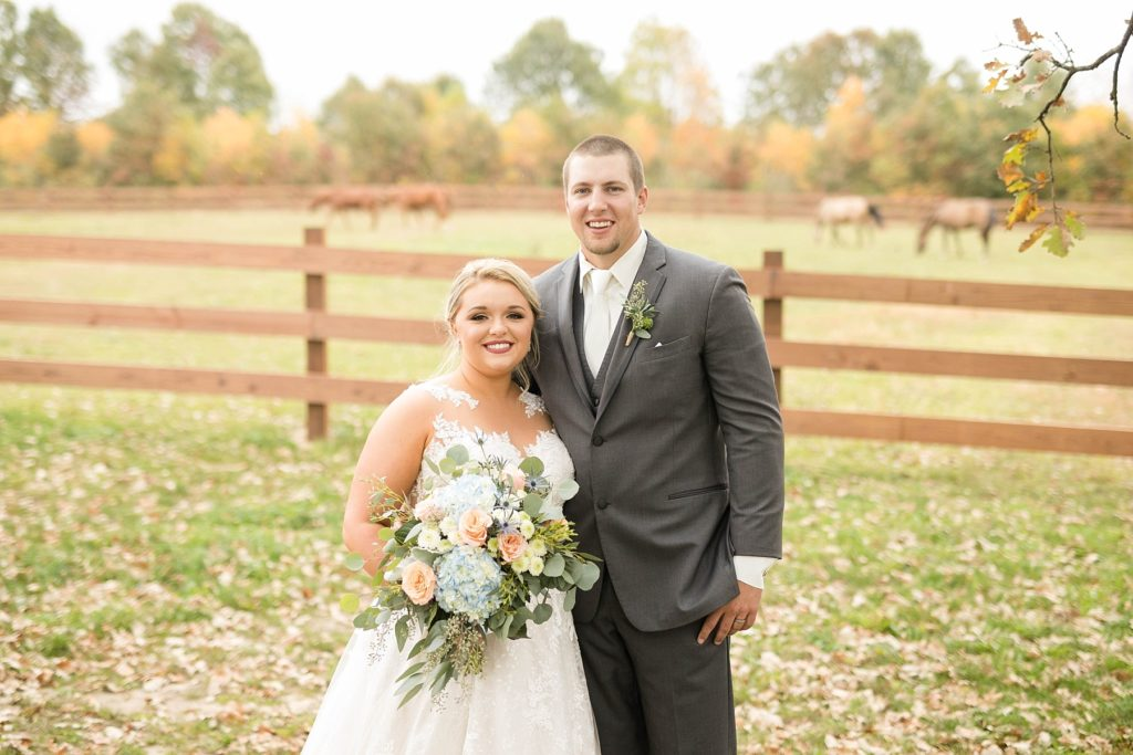 couple smile at the camera on their wedding day with horses in the pasture at their fall wedding at Lilydale in Chippewa Falls