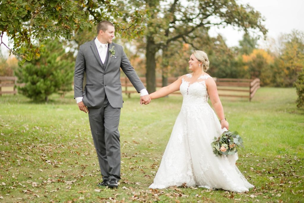 couple look at each other while walking to their reception at their fall wedding at Lilydale in Chippewa Falls