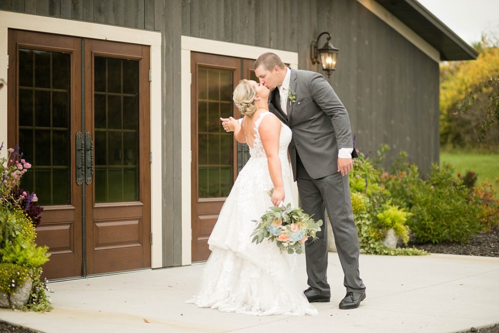 couple kiss outside the front doors at their fall wedding at Lilydale in Chippewa Falls