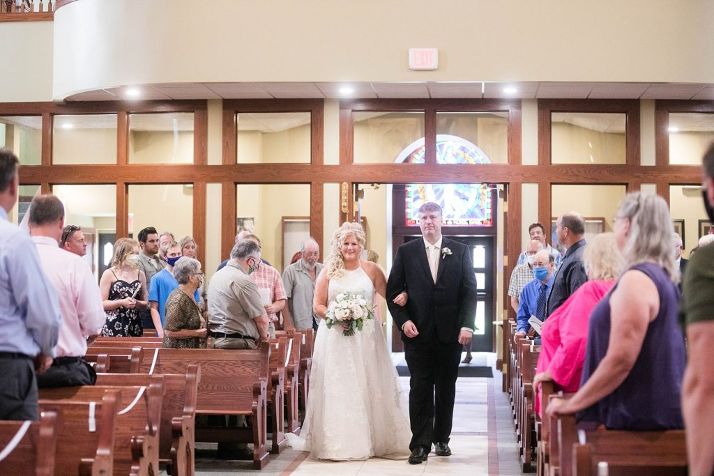 bride being walked down the aisle by her brother at Notre Dame Catholic Church in Chippewa Falls
