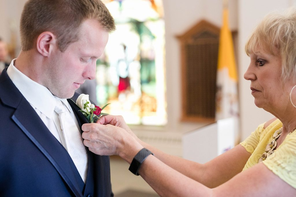 groom getting his flowers pinned on before the wedding ceremony at St. Charles Borromeo Catholic Church in Chippewa Falls