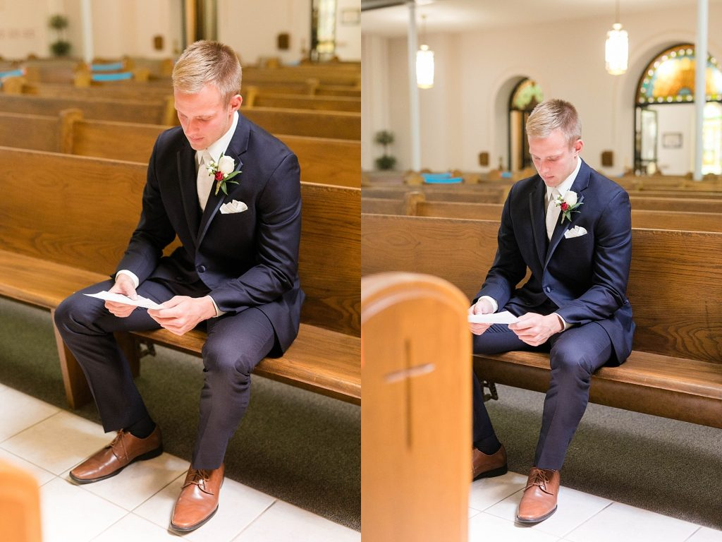 groom reading his letter from the bride in a church pew at St. Charles Borromeo Catholic Church in Chippewa Falls