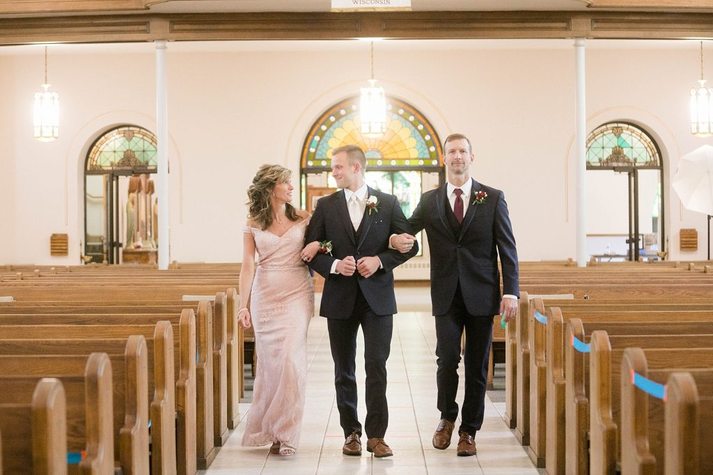 groom being walked down the aisle by both of his parents for an intimate wedding ceremony at St. Charles Borromeo Catholic Church in Chippewa Falls