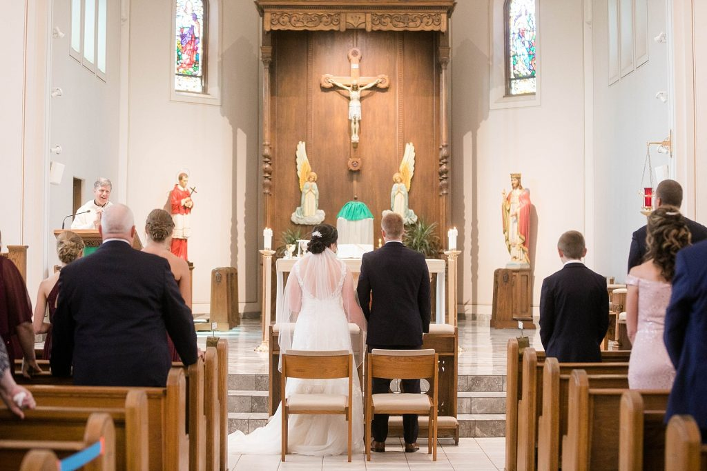 bride and groom during the homily at St. Charles Borromeo Catholic Church in Chippewa Falls