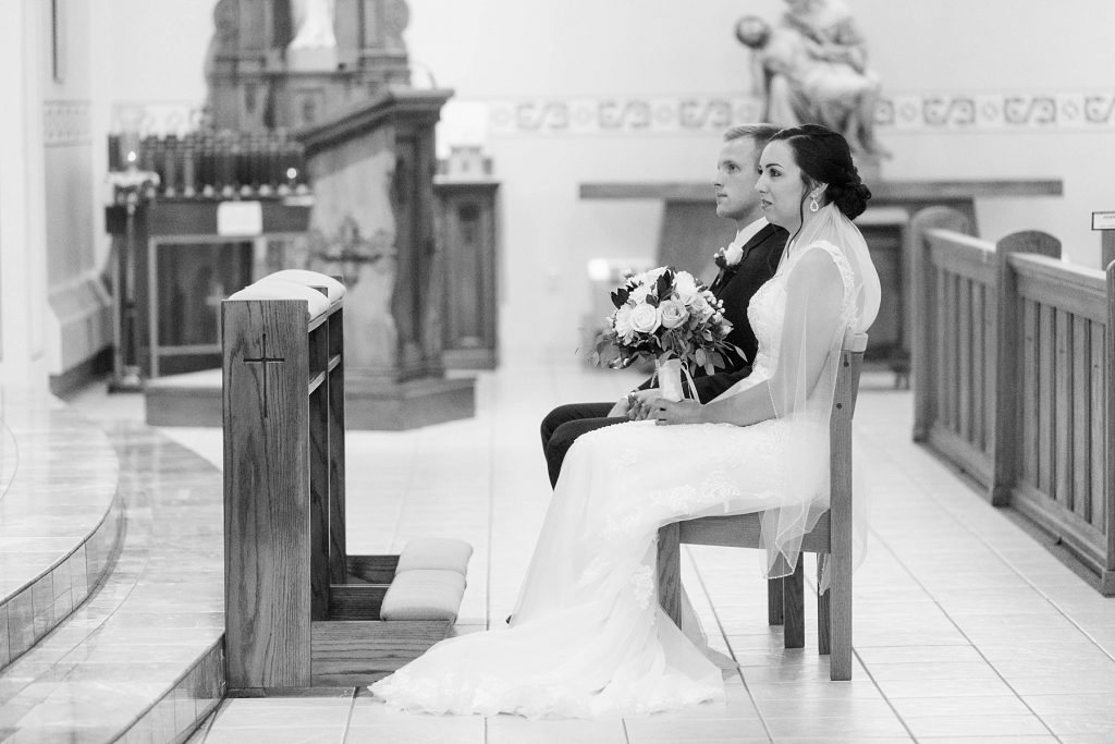 bride and groom sitting during the wedding ceremony at St. Charles Borromeo Catholic Church in Chippewa Falls