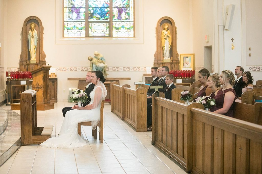 bride and groom and their guests during wedding ceremony at St. Charles Borromeo Catholic Church in Chippewa Falls