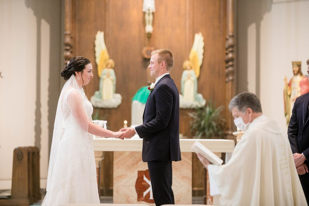 bride and groom holding hands during their wedding ceremony at St. Charles Borromeo Catholic Church in Chippewa Falls