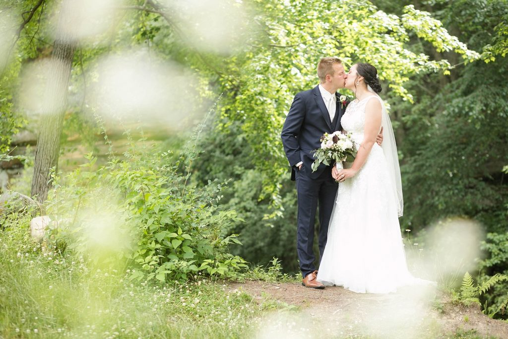 bride and groom kissing in the lush greenery  at Erickson Park in Chippewa Falls