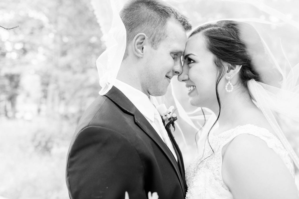 bride and groom nose to nose smiling at each other in a black and white photo  at Erickson Park in Chippewa Falls