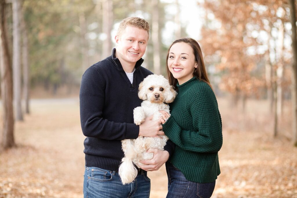 couple holding their dog standing outside in the leaves during the fall for an Eau Claire couple session with dog