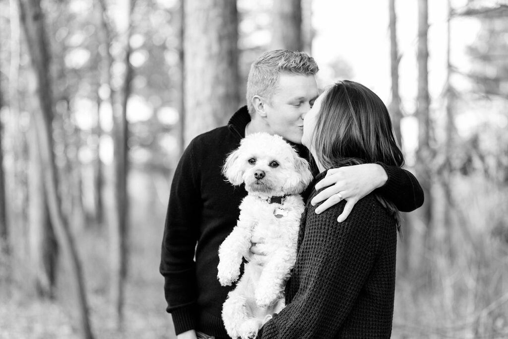 couple kissing in a black and white photo holding their dog for an Eau Claire couple session with dog