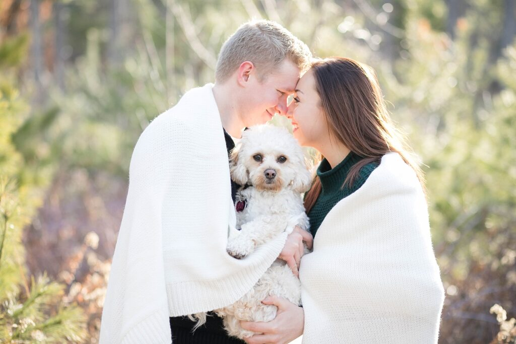 couple wrapped up in a blanket with their dog between them for an Eau Claire couple session with dog