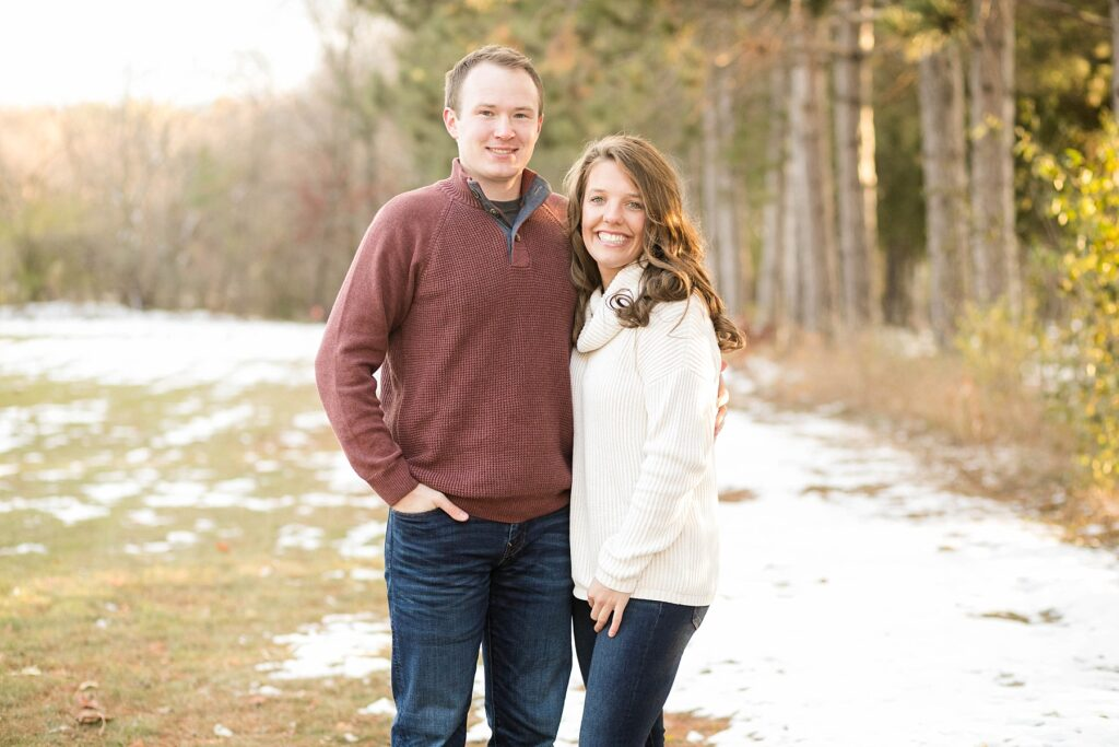 couple smiling in the snow for their Eau Claire couples session with new puppy