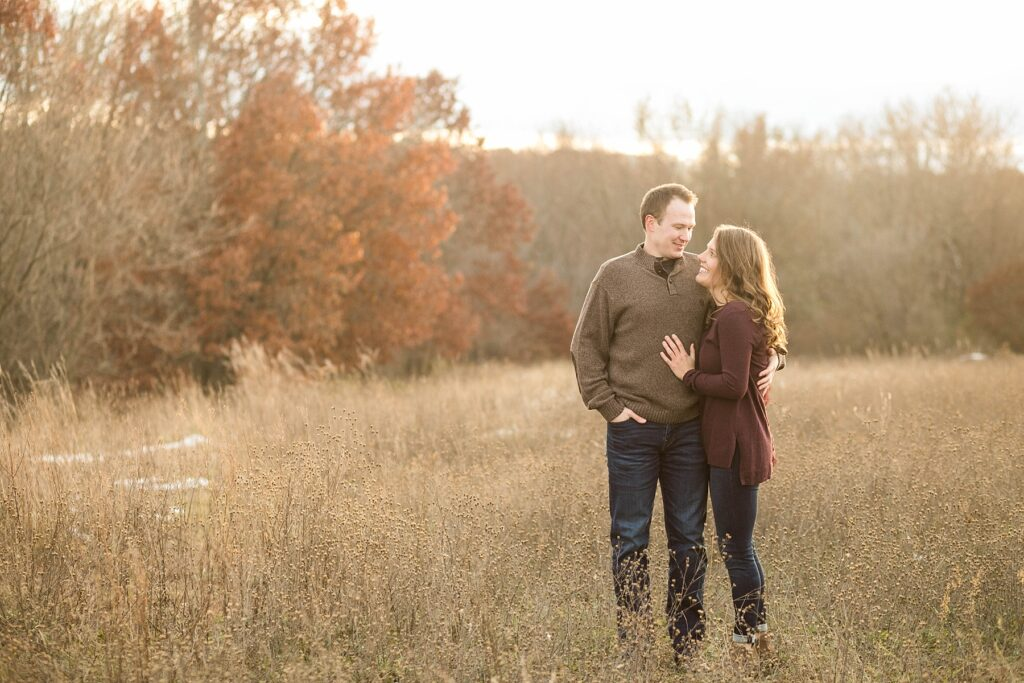 couple in a field during the fall for their Eau Claire couples session with new puppy