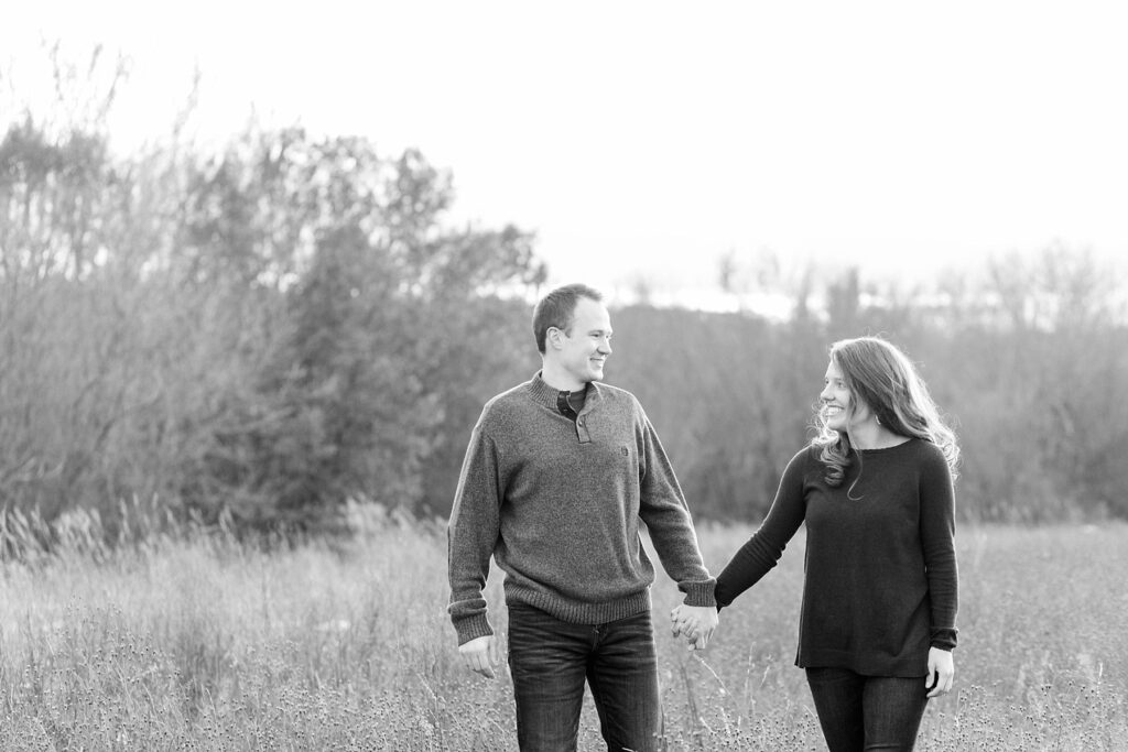 couple walking hand in hand in a black and white photo in a field for their Eau Claire couples session with new puppy