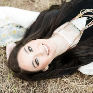 girl laying in a grassy field for her boho senior photos in Wisconsin