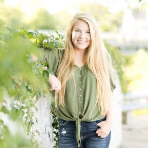 Rice Lake senior leans against a vine wall smiling in a green shirt and jeans.